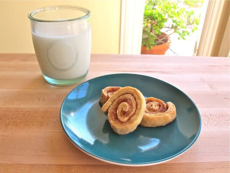 Three pie crust pinwheels on plate with milk.