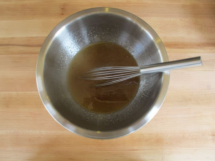Whisking oil, sugar, and eggs in a mixing bowl.