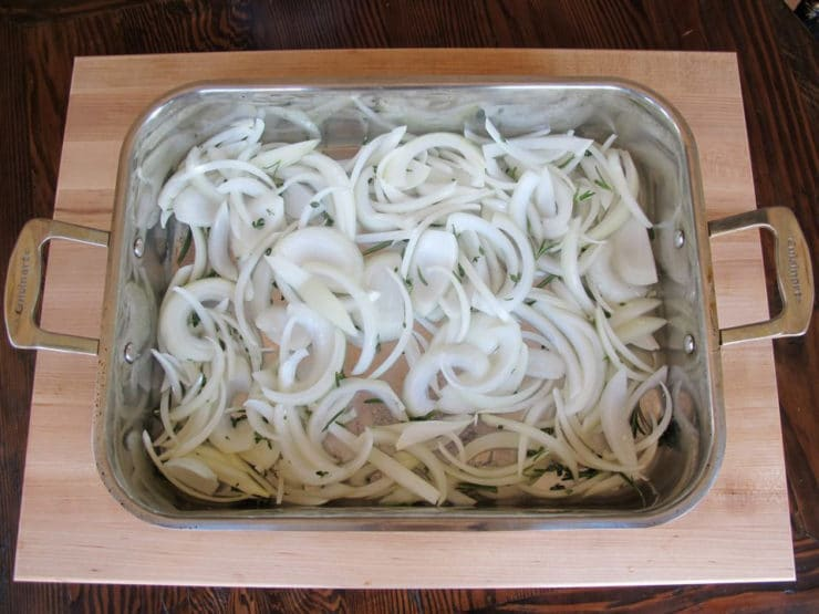 Sliced onions in a foil-lined baking pan.