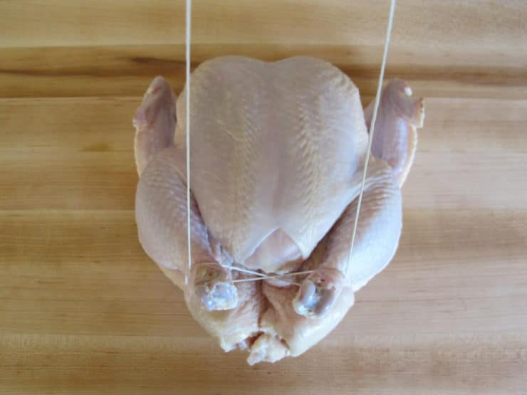 Whole chicken on cutting board - trussing strings looped around drumsticks.