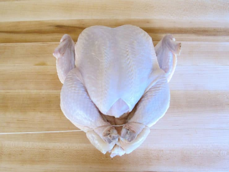Whole chicken on cutting board - trussing strings looped around drumsticks, pulling drumsticks tight together.