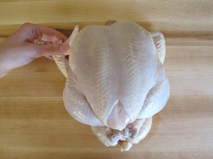 Trussed chicken, hand tucking wings behind back.