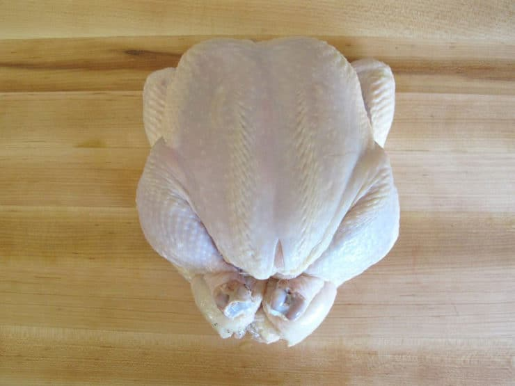 Fully trussed chicken on wooden cutting board.