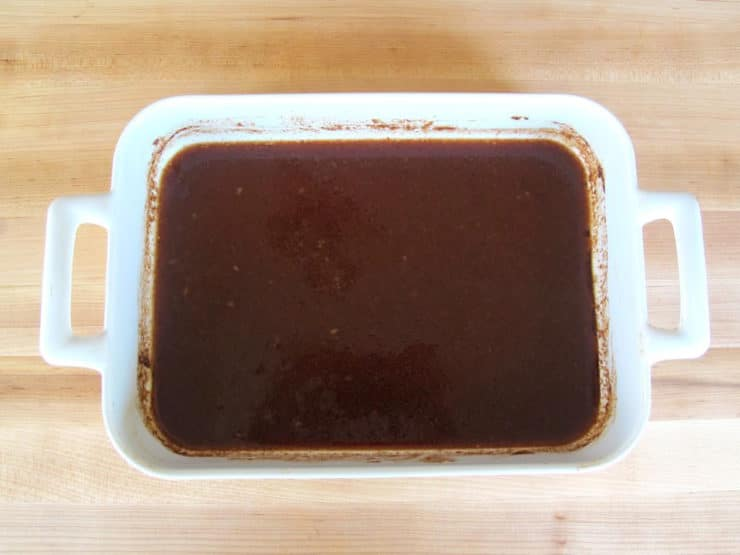 Water added to pomegranate molasses in a baking dish to thin.