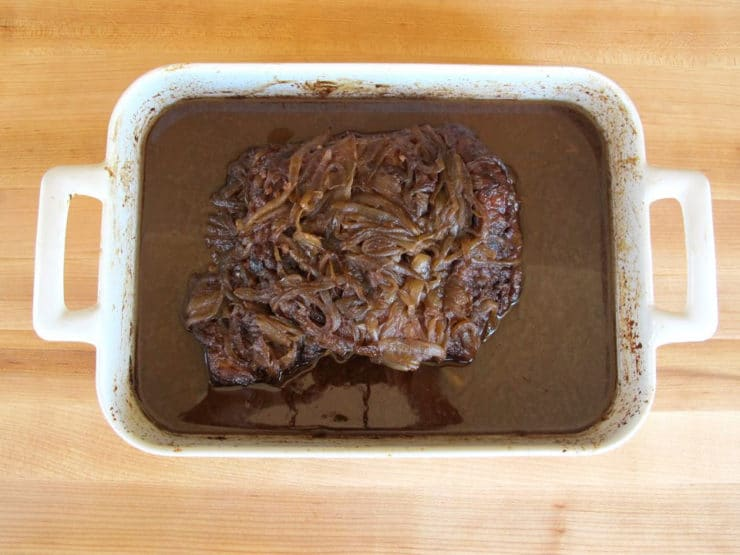 Cooked beef brisket in a roasting pan.