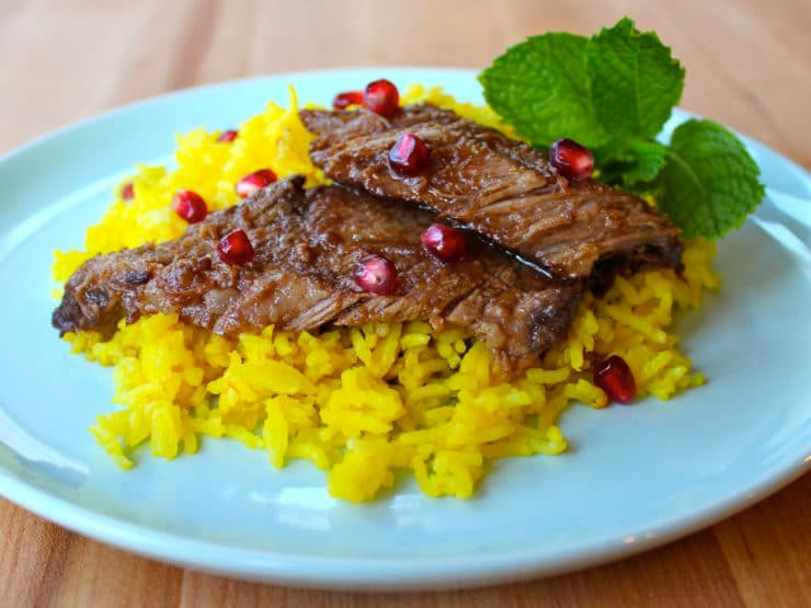Slices of Pomegranate Molasses Brisket on top of saffron rice with pomegranate arils and mint garnish on blue plate atop wooden cutting board.