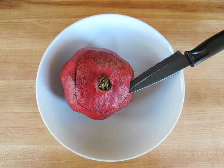 Carefully cutting the top end off a pomegranate.