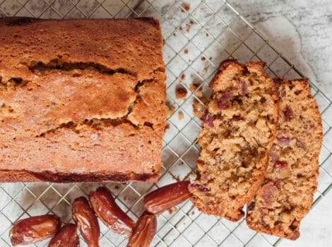 Featured square shot - sliced date honey nut cake on cooling rack with luscious dates on marble countertop.