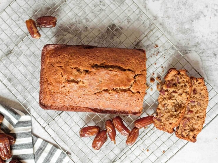 Wide horizontal shot - sliced date honey nut cake on cooling rack with luscious dates on marble countertop, striped linen towel laying beside the rack.