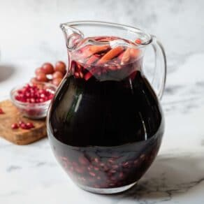 Square crop featured shot - Pitcher of dark burgundy Rosh Hashanah Sangria with apple slices and pomegranate arils floating on top, pomegranate seeds and grapes on a cutting board in background.