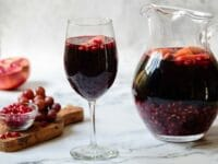 Horizontal shot - Glass of dark red Rosh Hashanah Sangria with a pitcher of sangria in background, each with fruit pieces floating on top. Wood cutting board with grapes and pomegranate arils, half a pomegranate in background.