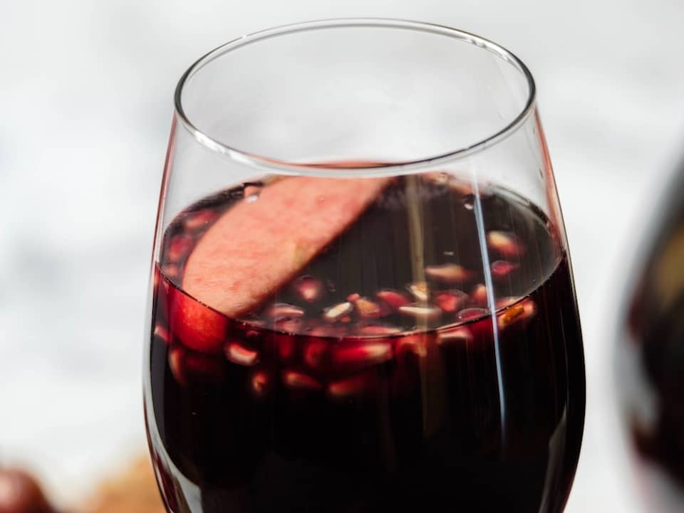 Close up horizontal shot - a wine glass of sangria with apple slices and pomegranate seeds floating on top.