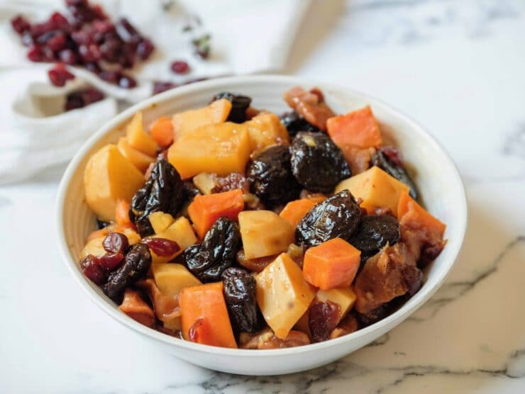 Horizontal shot - white bowl of tzimmes with sweet potatoes, prunes, carrots, and dried cranberries on a marble countertop, linen napkin with dried cranberries in background.