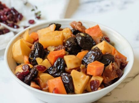 Square featured shot - white bowl of tzimmes with sweet potatoes, prunes, carrots, and dried cranberries on a marble countertop, linen napkin with dried cranberries in background.