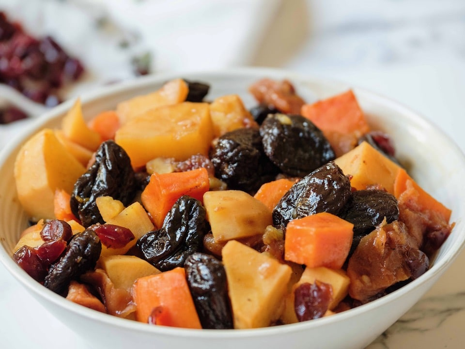 Close up over rim of bowl - white bowl of tzimmes with sweet potatoes, prunes, carrots, and dried cranberries on a marble countertop, linen napkin with dried cranberries in background.