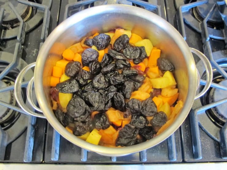 Pitted prunes added to stockpot of vegetables.