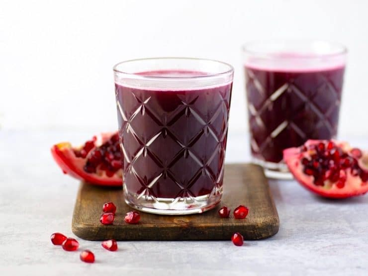 Two glasses of pomegranate juice surrounded by pomegranate slices and seeds on a wooden cutting board with marble background.