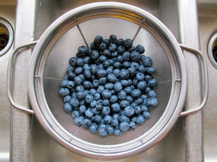 Rinsing fresh blueberries in a colander.