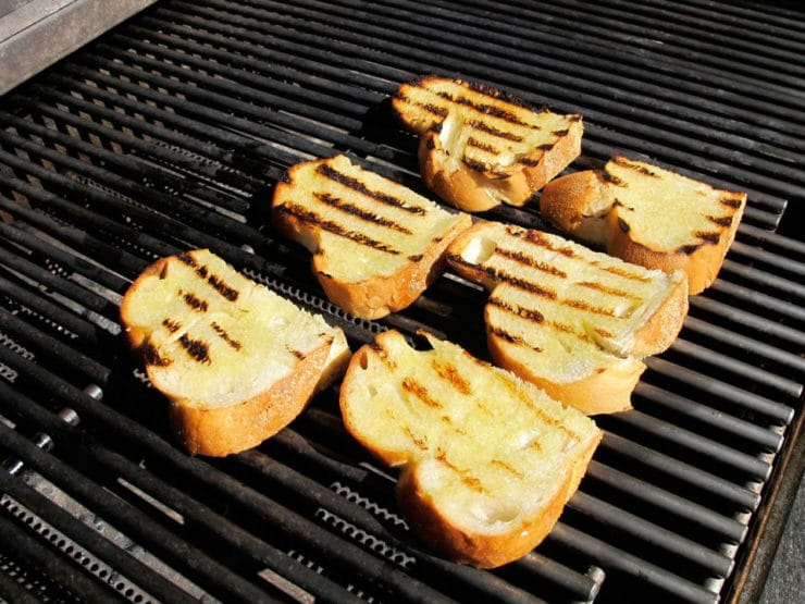 Toasting challah slices on a grill.