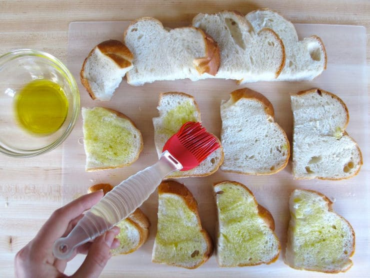 Brushing sliced challah with olive oil.