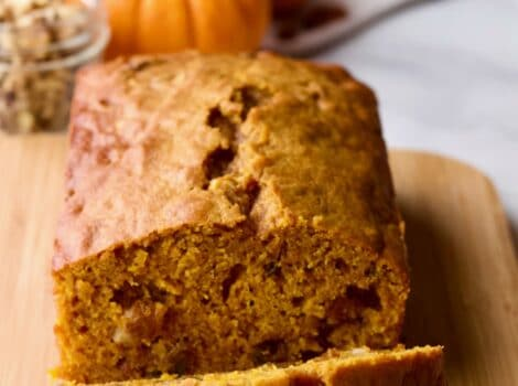 Featured Square Crop - Pumpkin Spice Cake Loaf on Cutting Board with pumpkin, raisins and spices in background on marble countertop.