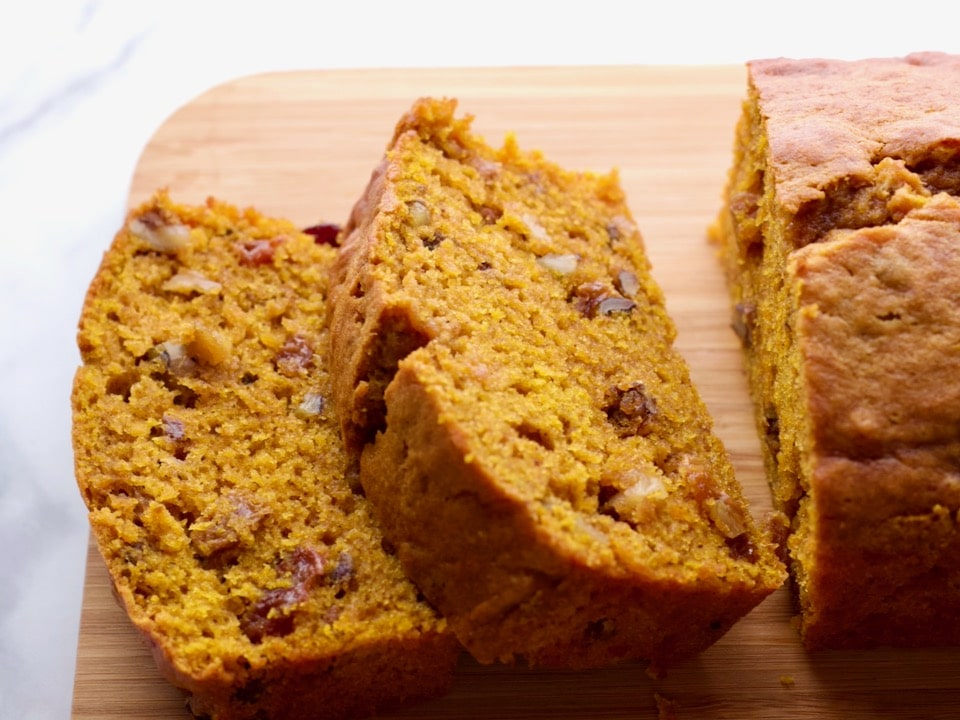 Front View - sliced pumpkin spice cake loaf on a wooden cutting board on marble countertop.