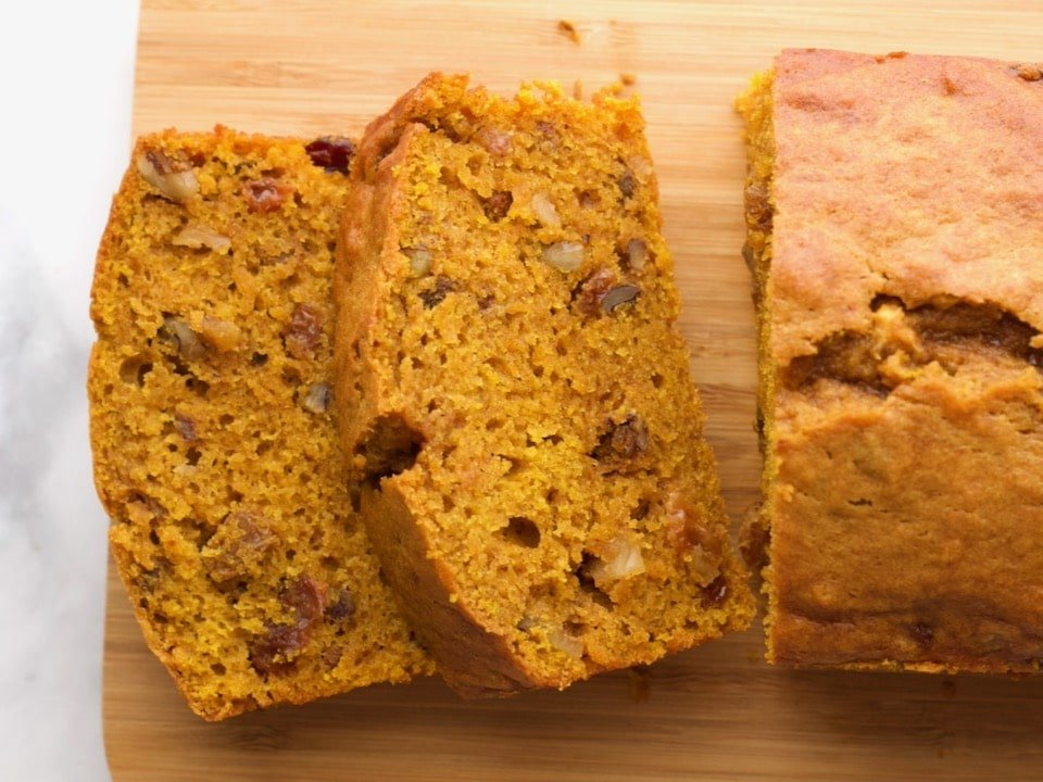 Overhead Shot - sliced pumpkin spice cake loaf on a wooden cutting board on marble countertop.