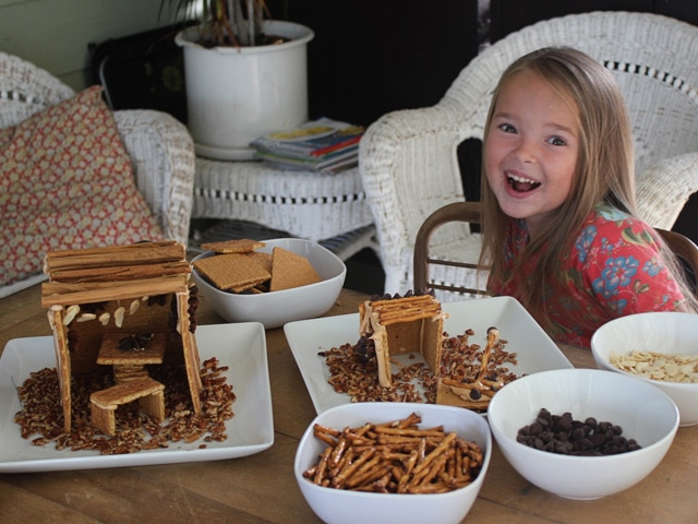 Smiling girl with food items to decorate her mini sukkah for Sukkot.