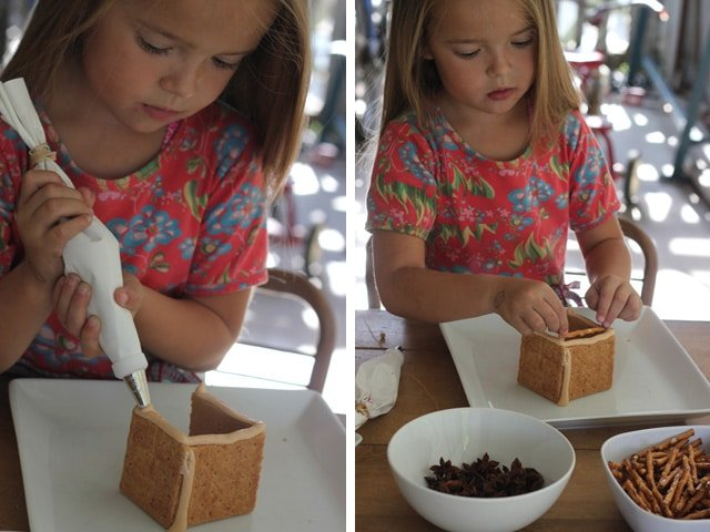 Little girl assembling mini sukkah from graham crackers and royal icing.