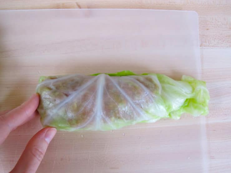 Rolling cabbage leaves around filling.