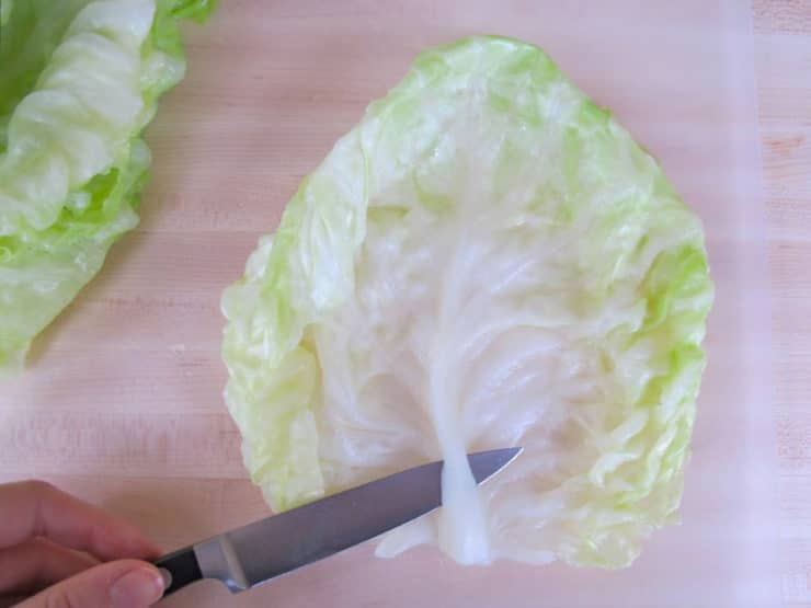 Removing tough stem from cabbage leaves.