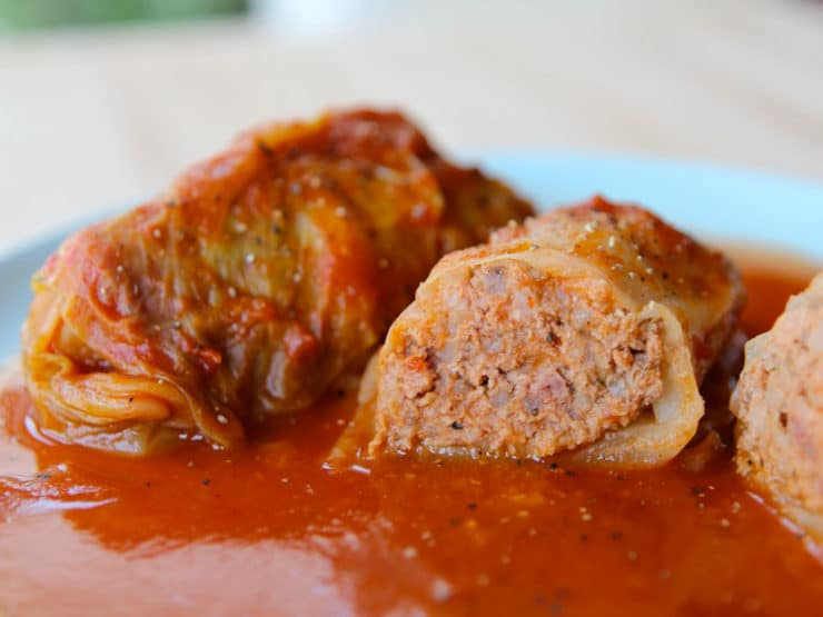 Two stuffed cabbage leaves, one cut in half, on a blue plate with sauce.