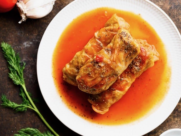 Three stuffed cabbage leaves - holishkes on a plate with sauce, fresh dill and garlic on the side.