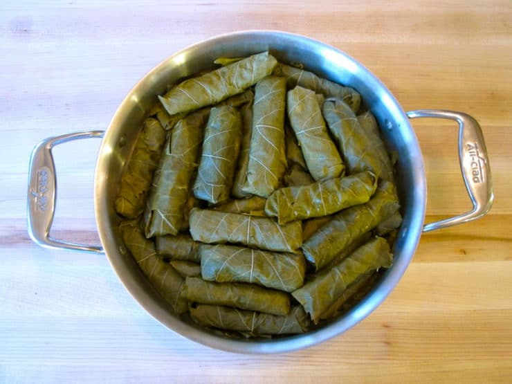 Layering stuffed grape leaves in a saute pan.