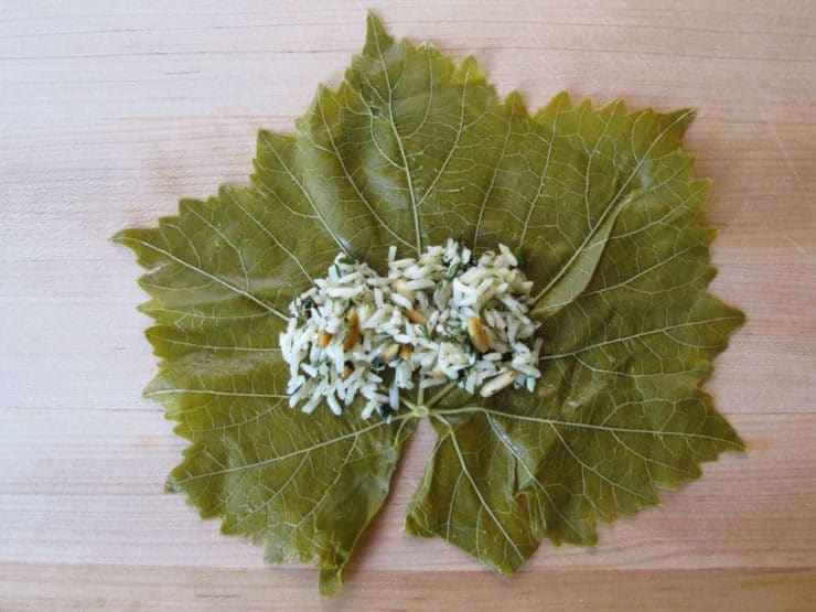 Filling placed on stem end of grape leaf.