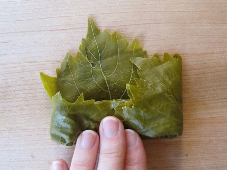 Fold grape leaf edges inward.