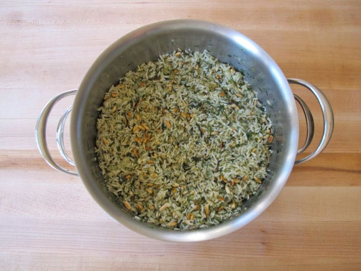 Seasoning and pine nuts stirred into rice.