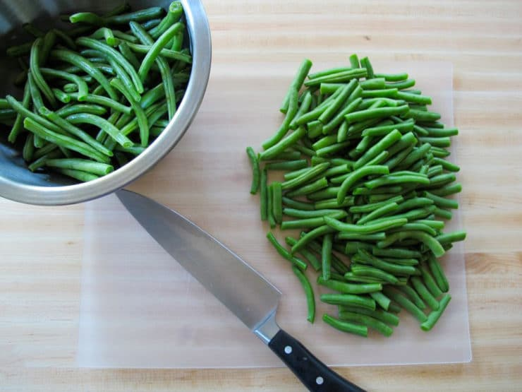 Cut green beans into 2-inch pieces on a cutting board.