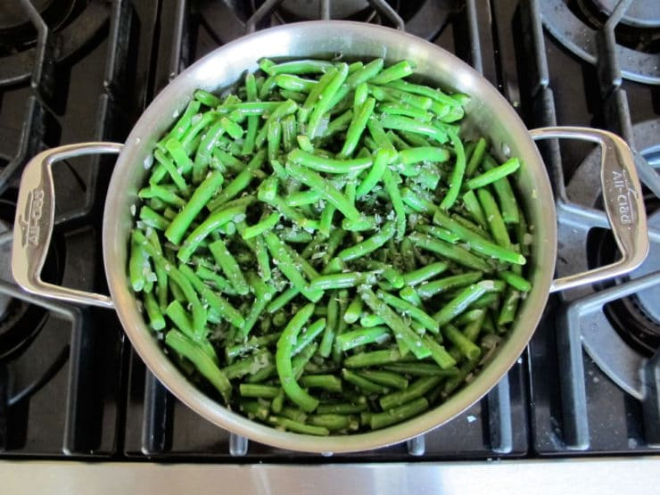 Cut green beans added to onions in skillet.