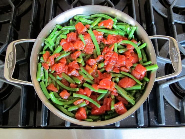 Tomatoes added to green beans in skillet.