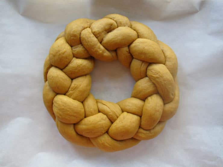 Braided challah circle on a parchment lined sheet.