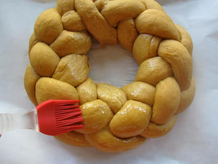 Brushing eggwash over braided challah circle.