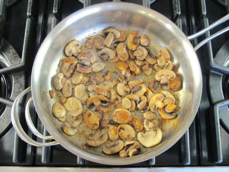Sliced mushrooms browning in a skillet.