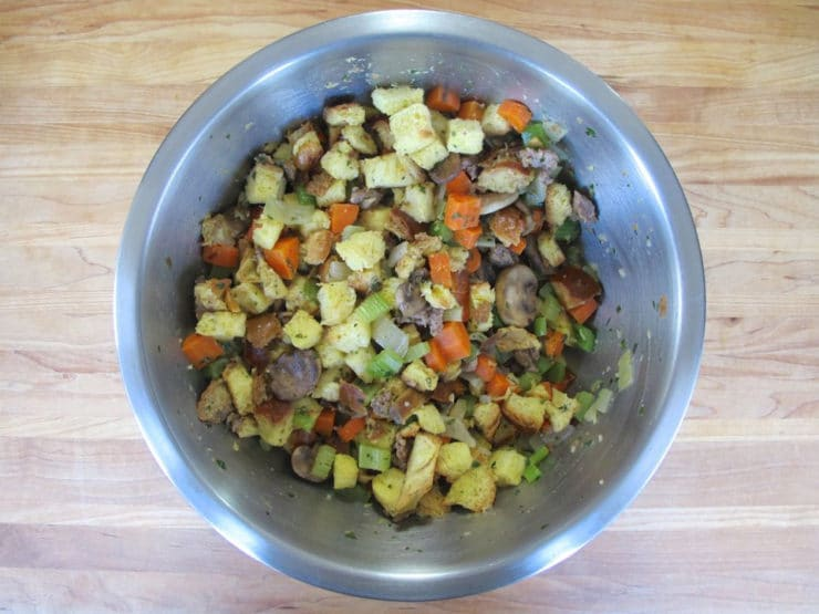 Challah cubes and sauteed vegetables tossed together in a large bowl.
