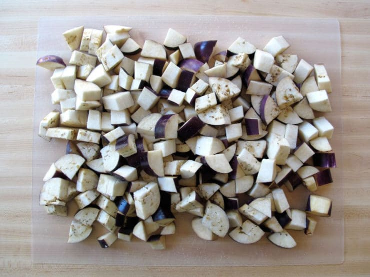 Cubed eggplant piled on a cutting board.