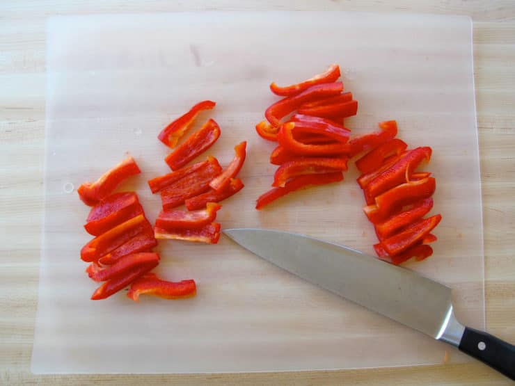 Thinly sliced red bell pepper on a cutting board.