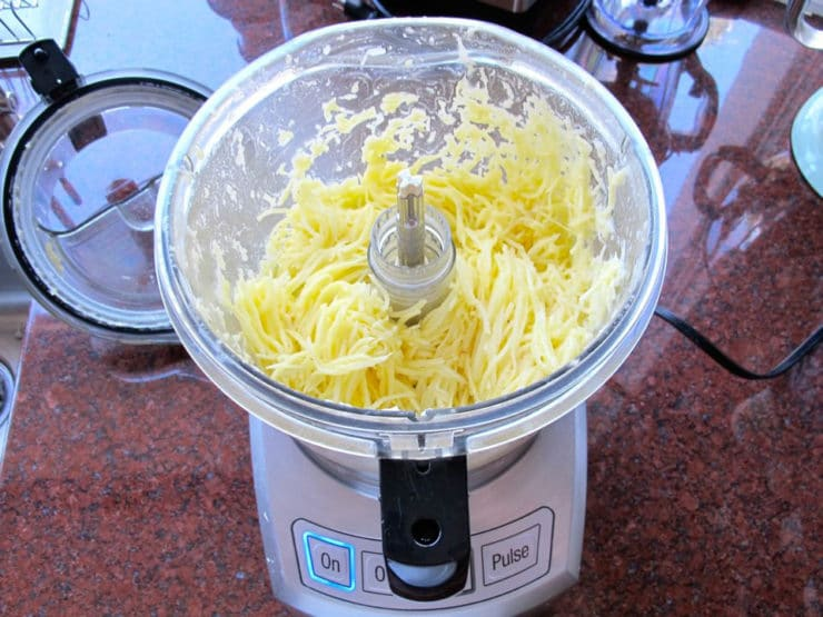 Grated potatoes in a food processor.