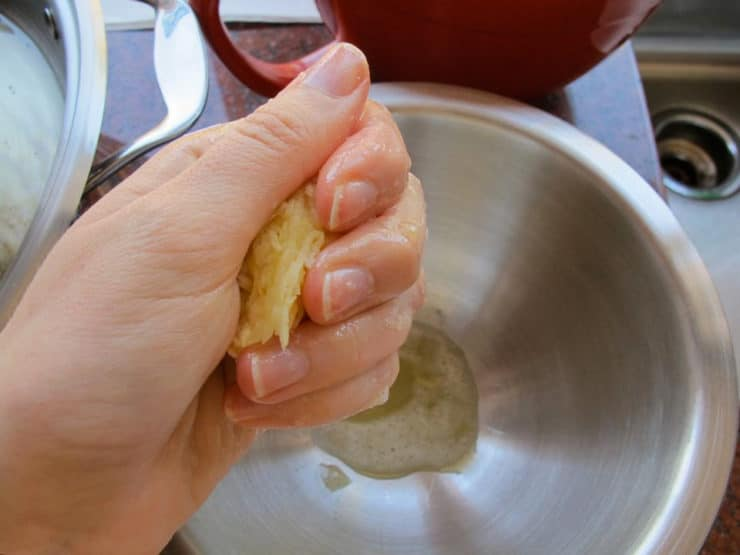 Squeezing moisture out of a latke.