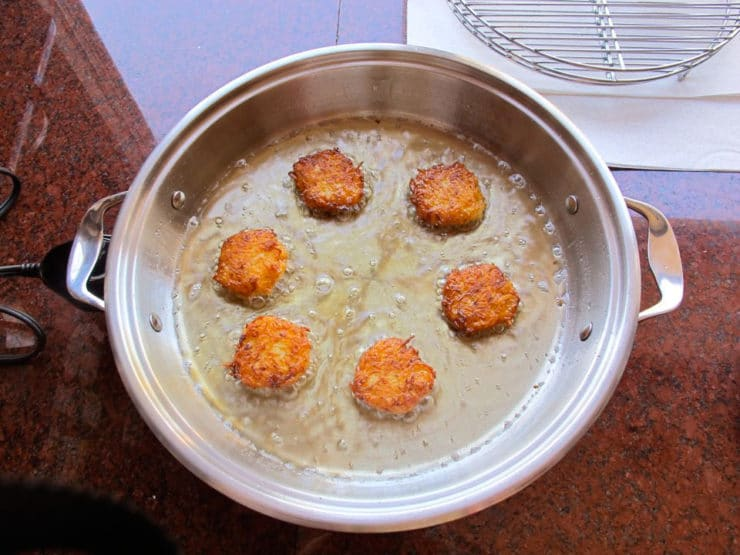 Frying latkes in oil in a skillet.