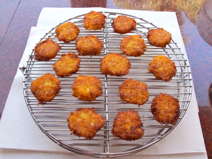 Latkes draining on a cooling rack over paper towels.